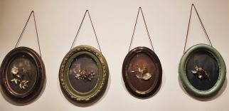 Natureza Morta 1 e 2, de Valéria Pena-Costa. Da Galeria Fuga. Medos e afetos são reunidos por meio de antigos porta-retratos de parede (que remetem à casa da avó) com pássaros mortos empalhados ao lado de arranjos florais de prata e pedras semipreciosas; um olhar fúnebre e imortalizado sobre a memória e a morte dentro do ambiente familiar.