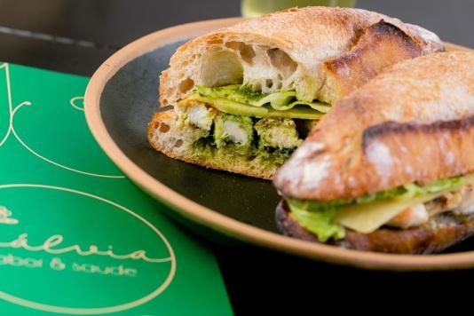 Pesto sub (sanduíche com tiras de frango, alface americana, tomate ao pesto de manjericão e rúcula, lâminas de queijo parmesão, servido em pão baguete de fermentação natural, R$ 22)